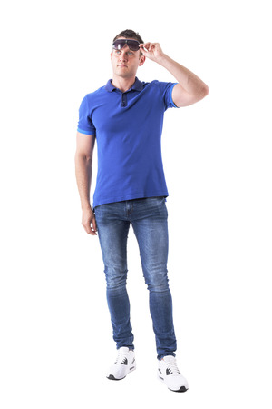 Adult man in casual clothes holding sunglasses and looking up interested. Full body isolated on white background. Stock Photo