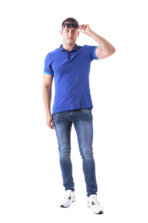 Front view of young adult casual man remove sunglasses and looking at distance. Full body isolated on white background.