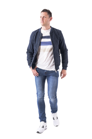 Front view of confident casual masculine man in jeans and jacket walking and looking up. Full body isolated on white background.