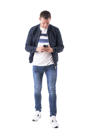 Front view of young adult casual man using and looking down at mobile phone. Full body isolated on white background.