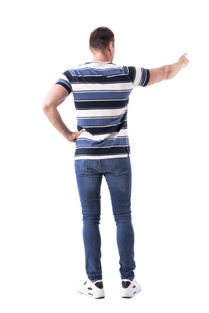Back view of adult casual man pointing finger and showing direction. Full body isolated on white background. Фото со стока