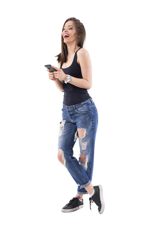 Pretty modern young woman laughing heartily white holding cellphone in trendy torn jeans. Full body isolated on white background.