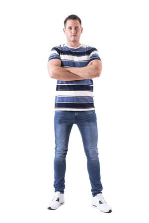 Serious successful man with blank facial expression looking at camera with crossed arms. Full body isolated on white background.
