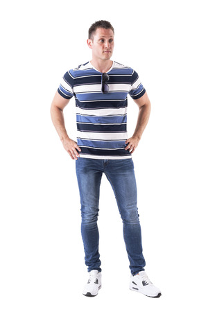 Confused young man in casual clothes with hands on hips looking away doubtfully. Full body isolated on white background.