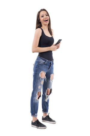 Beautiful young woman in tank top and jeans holding mobile phone and laughing. Full body isolated on white background. 版權商用圖片