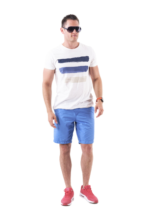 Confident serious macho man in summer shorts with sunglasses walking forward. Full body isolated on white background.