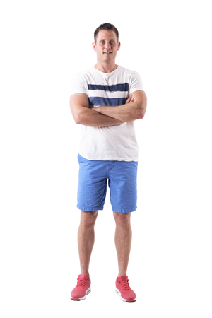 Happy relaxed man wearing t-shirt and shorts with crossed arms smiling. Full body isolated on white background.