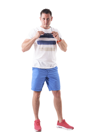 Upset adult tough man removing sunglasses and staring at camera. Full body isolated on white background. Stok Fotoğraf