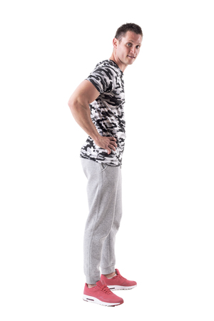Side view of handsome man posing and smiling at camera in sporty clothes. Full body isolated on white background.