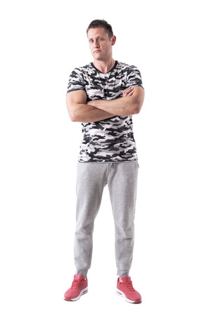 Frustrated adult distrustful man with crossed arms looking at camera. Full body isolated on white background.