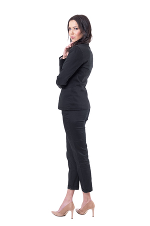 Back side view of elegant sexy business woman turning and looking at camera in black suit. Full body isolated on white background.