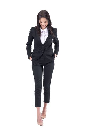 Candid relaxed business woman with hands in suit pockets walking and laughing while looking down. Full body isolated on white background.