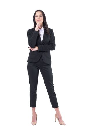 Confident elegant business woman in black suit with hand on chin looking at camera. Full body isolated on white background.