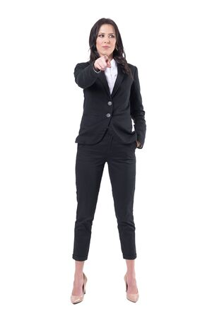 Distracted formal business woman pointing finger at camera but looking away. Full body isolated on white background.