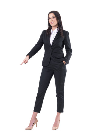 Happy successful business woman pointing finger and showing down smiling at camera. Full body isolated on white background.