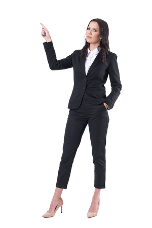 Serious confident businesswoman pointing finger up doing presentation. Full body isolated on white background.