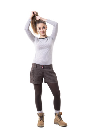 Funny expressive cute in retro styled clothes making hairdo herself. Full body isolated on white background.