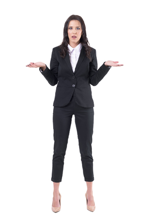 Communication problems concept. Shocked confused young business woman shrugging shoulders. Full body isolated on white background.