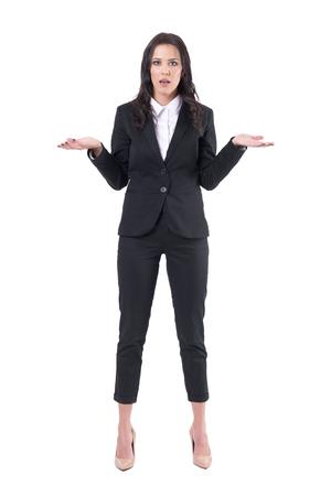 Koncepcja problemów komunikacyjnych. Zszokowana młoda biznesowa kobieta wzrusza ramionami. Całe ciało na białym tle.