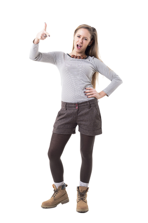 Rebellious young hipster woman pointing finger at camera accusing or blaming. Full body isolated on white background. 版權商用圖片