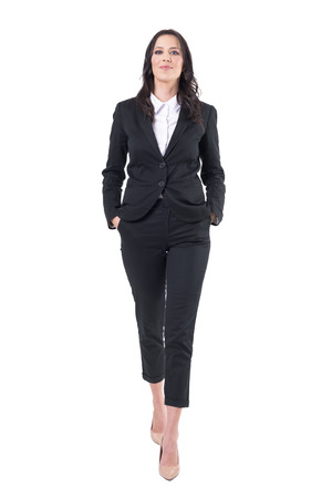 Confident successful business woman walking towards camera with hands in pockets. Full body isolated on white background. Stock Photo