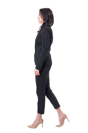 Profile view of elegant business woman in suit stepping forward. Full body isolated on white background.