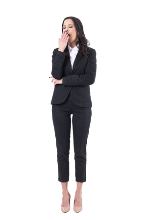 Tired sleepy overworked business woman in black suit yawning with closed eyes. Full body isolated on white background.