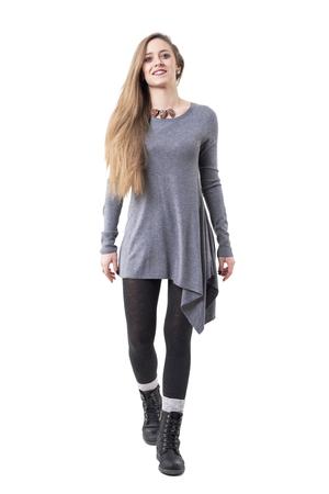 Vista frontal de la mujer elegante joven feliz en túnica gris caminando hacia la cámara. Cuerpo completo aislado sobre fondo blanco.