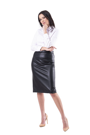 Slim sexy elegant business woman looking at camera with hand on chin. Full body isolated on white background.