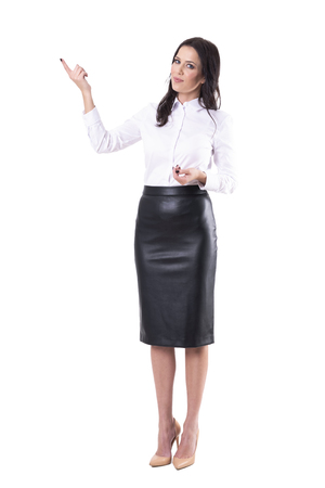 Smiling friendly business woman or saleswoman pointing up showing copyspace. Full body isolated on white background.