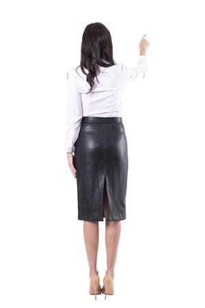 Vista posterior de la joven profesora o mujer de negocios que señala el dedo que muestra el espacio vacío de la copia. Cuerpo completo aislado sobre fondo blanco.