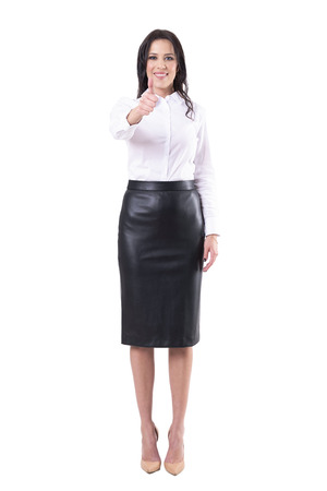 Happy satisfied smiling young adult business woman showing thumb up at camera. Full body isolated on white background.