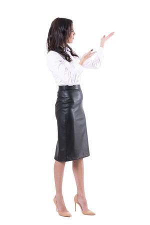 Joven profesora o mujer de negocios que presenta o muestra el espacio de la copia en blanco. Cuerpo completo aislado sobre fondo blanco.