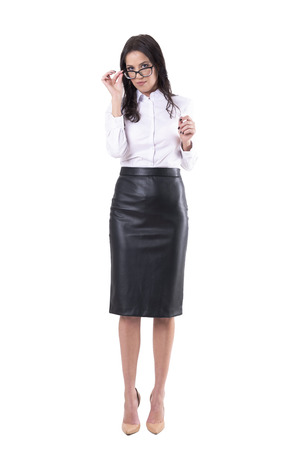 Serious business woman or teacher adjusting or applying eye glasses looking at camera. Full body isolated on white background. Stock Photo