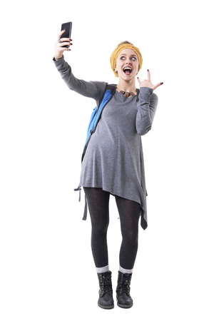 Cool playful excited young backpacker woman taking selfie with rock n roll gesture. Full body isolated on white background. Stockfoto - 123064999