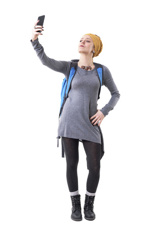 Cool proud confident woman backpacker hiker taking selfie with cellphone after success. Full body isolated on white background.