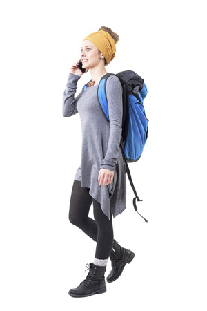 Cheerful excited young traveler woman with backpack walking and talking on the mobile phone. Full body isolated on white background. Stockfoto - 123065001