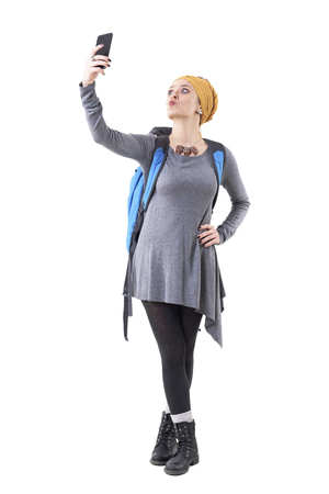 Cool playful millennial hipster tourist woman backpacker sending kiss taking selfie with phone. Full body isolated on white background. Stockfoto