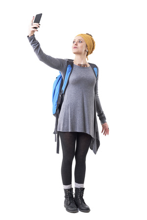 Cute relaxed young backpacker woman explorer taking pictures with mobile phone. Full body isolated on white background. 写真素材