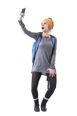 Cool cheerful carefree young hipster traveler girl taking selfie screaming of excitement. Full body isolated on white background. Stockfoto - 123065018