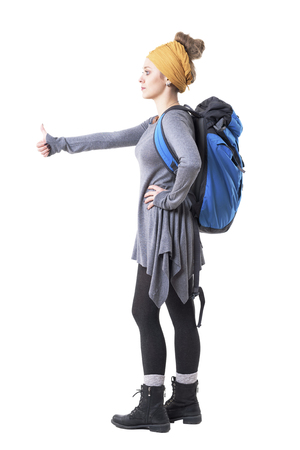 Side view of cool stylish hipster young woman with backpack hitchhiking and looking away. Full body isolated on white background. Stockfoto - 123065040
