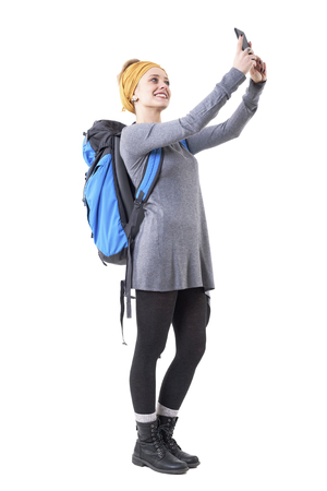 Relaxed happy traveling young woman with rucksack taking selfie with smartphone. Full body isolated on white background.