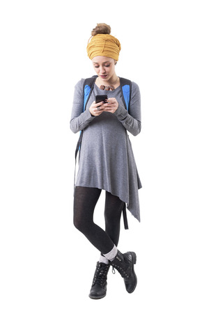 Cool modern stylish hipster traveler woman with rucksack reading messages on cellphone. Full body isolated on white background.