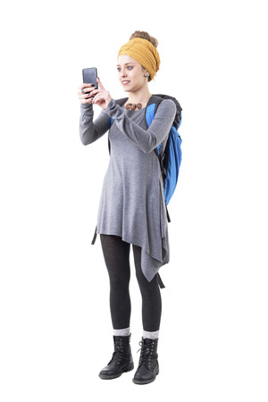 Happy young hipster tourist woman with backpack sightseeing and taking photo with smart phone. Full body isolated on white background.