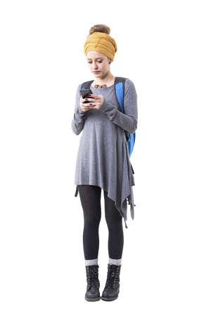 Young hipster backpacker woman adventurer using smart phone carrying rucksack. Full body isolated on white background.