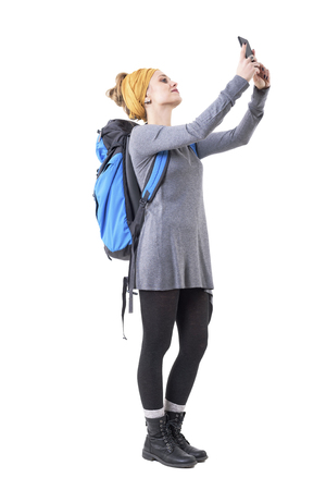Young hipster girl tourist with backpack taking photos with smartphone looking away. Full body isolated on white background. Stockfoto - 123065058