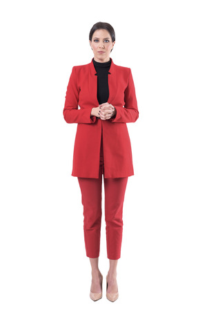 Formal young business woman in red suit with clasped hands looking at camera. Full body isolated on white background. Stockfoto