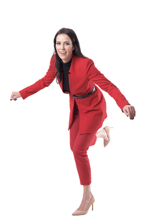 Attractive young business woman in red suit and high heels stumbling and falling. Full body isolated on white background. Banque d'images
