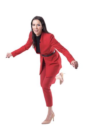 Jolie jeune femme d'affaires en costume rouge et talons hauts trébuchant et tombant. Corps entier isolé sur fond blanc.