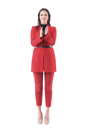 Young business woman in elegant red suit congratulating and applauding in standing ovations. Full body isolated on white background.